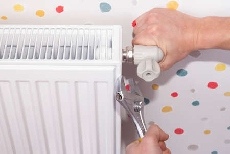 plumber connects steel radiator to the heating system