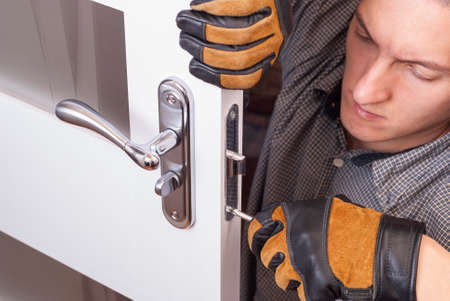 handyman repair the door lock in the room 스톡 콘텐츠