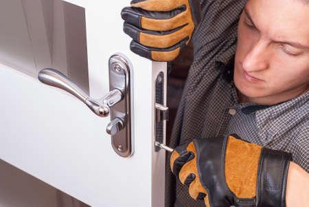 Tuttofare riparare la serratura della porta nella stanza Archivio Fotografico - 69160807