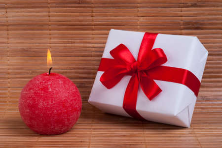 gift with red ribbon and candle on bamboo background