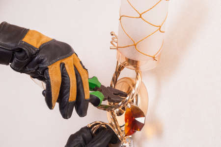 sconce: electrician with pliers in his hand repairing a sconce Stock Photo
