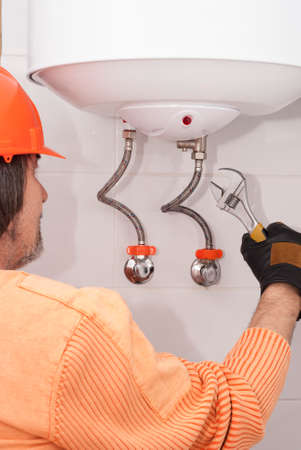 man holding wrenches and connects plumbing fittings