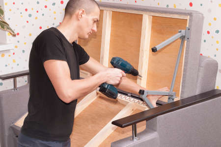 Worker at home repairing a folding sofa