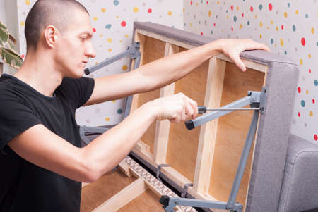 worker at home repairing a folding sofa Stock Photo