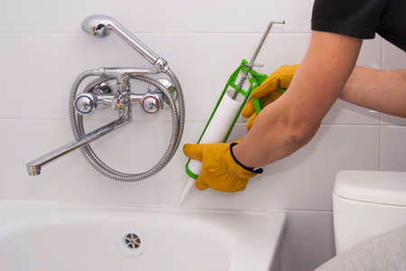 plumber apply silicone sealant to the joint bathtubs and ceramic tile