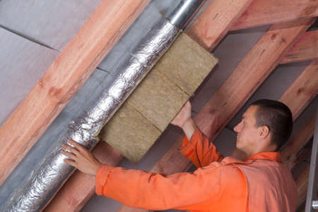 attic: installer wraps the air duct with mineral wool and foil