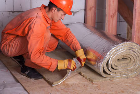 attic: worker cuts off a strip of mineral wool Stock Photo