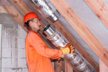 worker in the attic connects metal air ducts