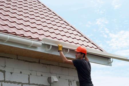 労働者は屋根の上の溝システムをインストールします。