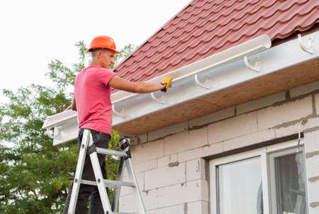 Il lavoratore installa il sistema di grondaia sul tetto Archivio Fotografico - 82956157