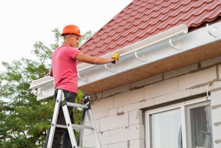 worker installs the gutter system on the roof