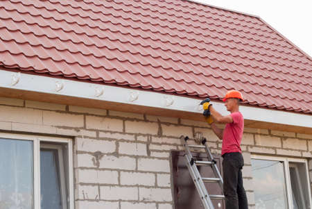 roofing system: worker installs the gutter system on the roof