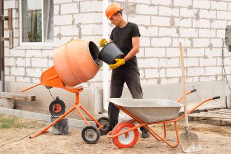 Travailleur de la construction avec un seau dans ses mains charge un mélangeur de béton