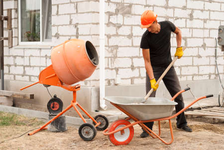 construction worker with a shovel in his hands loads a concrete mixer 스톡 콘텐츠