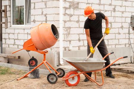 Bouwvakker met een schop in zijn handen laadt een betonmixer