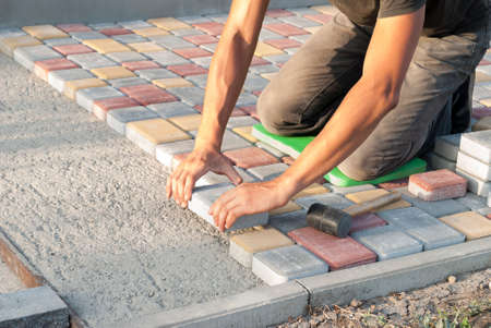construction worker laying sidewalk tiles in the yard of the house Banco de Imagens