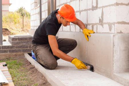 Arbeiter appliziert Bitumenmastix auf dem Fundament