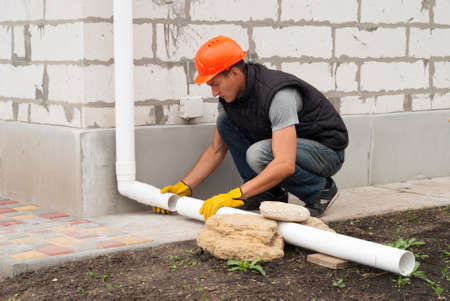 Construction worker installs pipe the gutter system