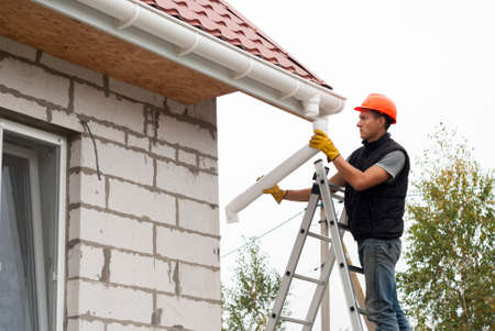 Worker installs the gutter system on the roof Stockfoto