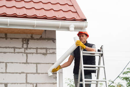 Construction worker installs the gutter system on the roof