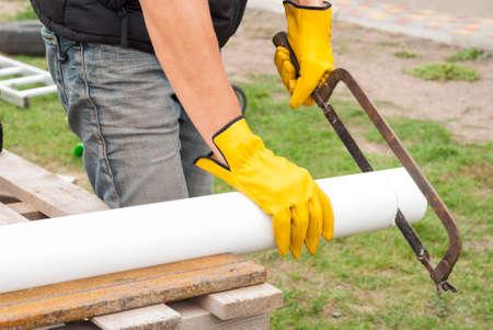 Construction worker cuts the pipe gutter system Reklamní fotografie