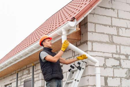 Pracownik budowlany instaluje system rynnowy na dachu