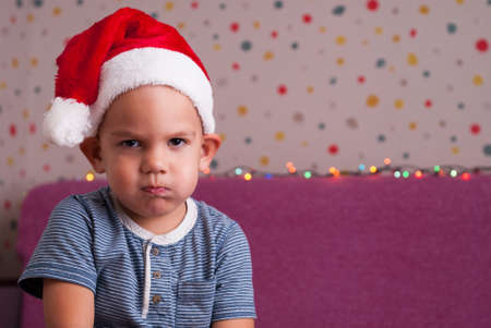 boy in a santa hat angrily looks