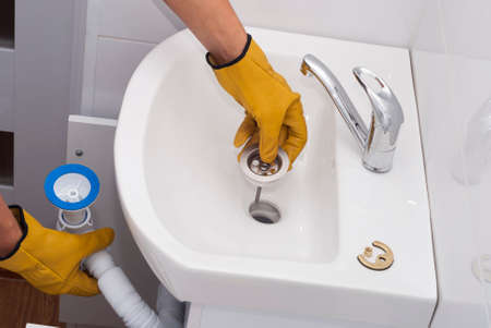 plumber installs a new plastic siphon on the sink 免版税图像