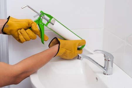 L'idraulico riempie la giunzione tra il lavello e la piastrella con un sigillante siliconico Archivio Fotografico - 89936016