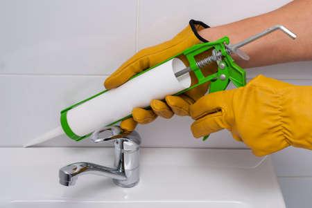 配管工はシリコーン シール剤でシンクとタイルの間の縫い目を塗りつぶします
