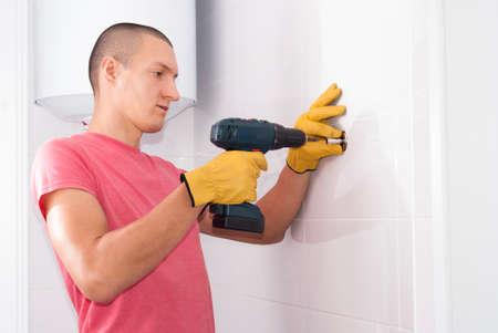 man is installing a towel heater bracket on the wall