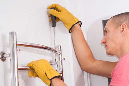 L'uomo installa un portasciugamani riscaldato elettrico nel bagno Archivio Fotografico - 90805236