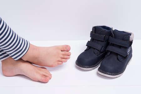 calçados e pés das crianças no fundo branco