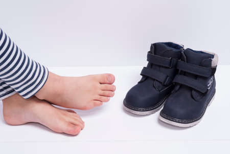 children's shoes and feet on white background
