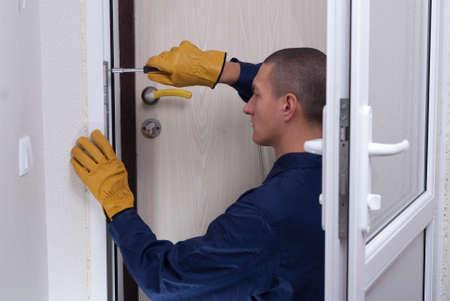 master of installation and repair of door locks at work Standard-Bild