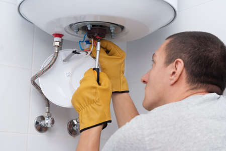 repairman for an electric boiler connects the wires to a thermostat