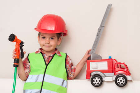 little boy in a red helmet and with a hose in his hands imagines himself to be a fireman Stock Photo