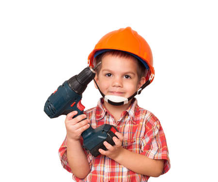 little boy imagines himself a construction worker in a helmet and with a screwdriver in his hand