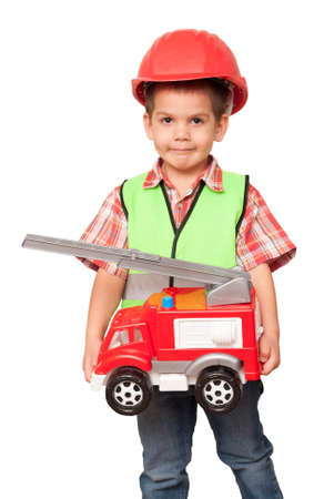 little boy with a fire engine in his hands and in a red helmet imagines himself to be a fireman