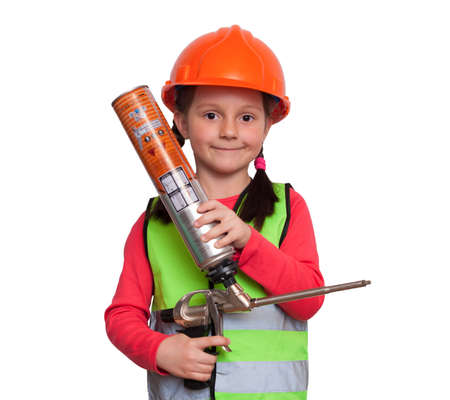 little girl in uniform and helmet holds a gun with mounting foam and imagines herself an industrial worker Stock Photo