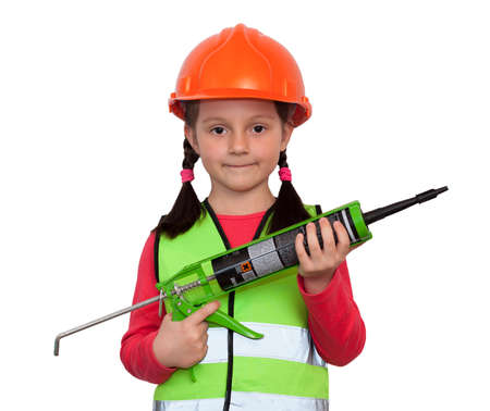 little girl in uniform and helmet holds a pistol with a bitumen sealant and imagines herself an industrial worker