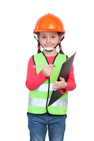 A little girl in industrial worker uniform wearing a helmet. Holding a tablet and a pen Stock Photo