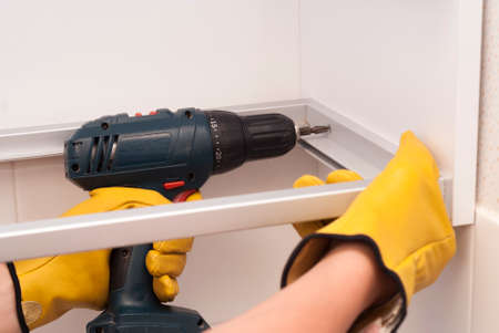 worker with screwdriver assembles and installs furniture in the kitchen