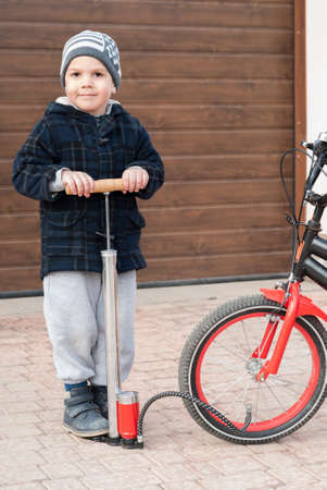 little boy inflates bicycle wheel with a hand pump Banco de Imagens