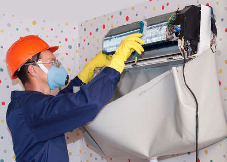 professionele werker reinigt de binnenunit van de airconditioner Stockfoto