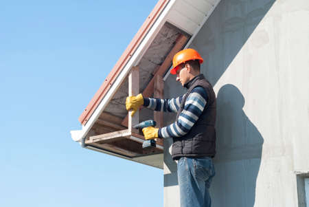 construction worker mounts a soffit on the roof eaves Stock Photo