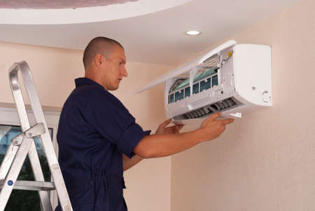 master installs indoor unit of the air conditioner