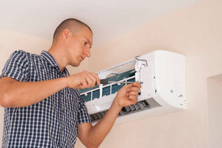 worker installs the indoor unit air conditioner on the wall