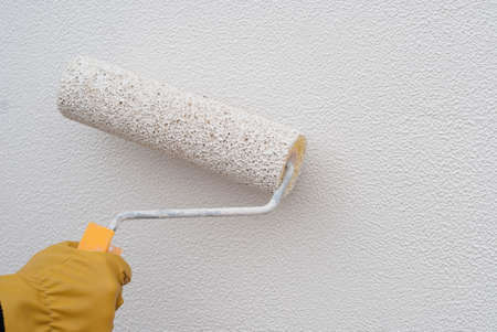 structural roller in hand on the background of painted wall