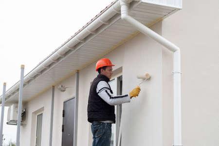 operaio edile sta dipingendo un muro con un rullo a